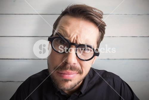 Composite image of portrait of a doubtful businessman with glasses