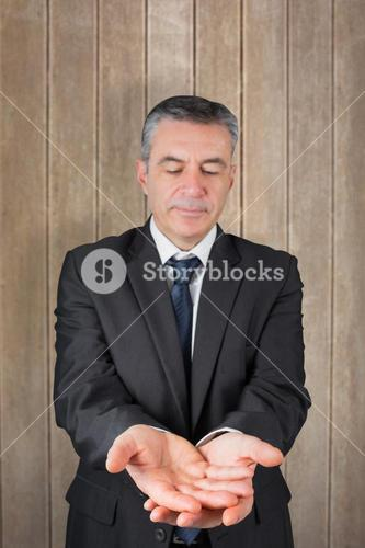 Composite image of mature businessman holding his hands out