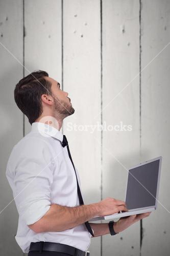 Composite image of sophisticated businessman standing using a laptop