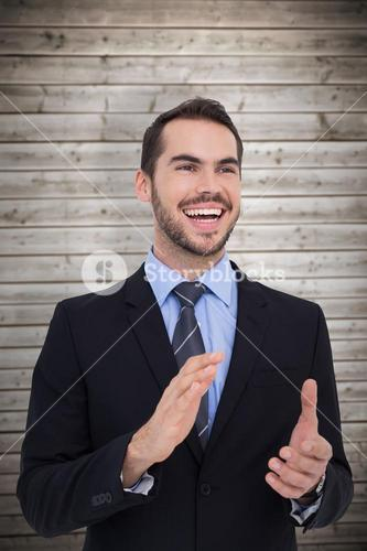 Composite image of happy businessman standing and clapping