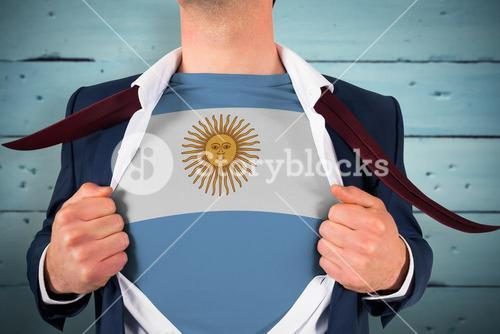 Composite image of businessman opening shirt to reveal argentina flag