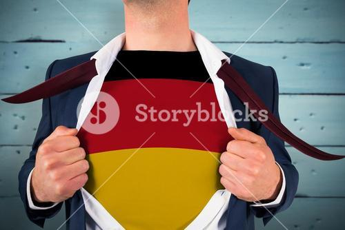 Composite image of businessman opening shirt to reveal germany flag