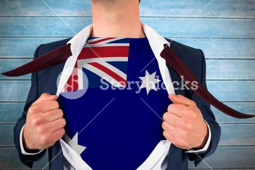 Composite image of businessman opening shirt to reveal australia flag