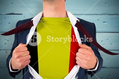 Composite image of businessman opening shirt to reveal belgium flag