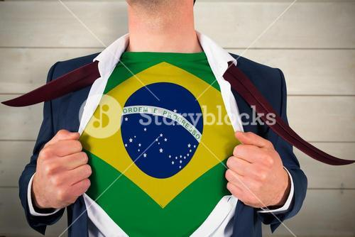 Composite image of businessman opening shirt to reveal brasil flag