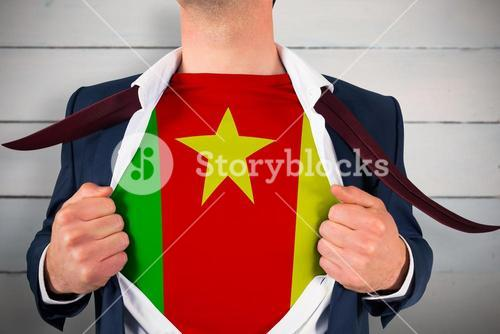 Composite image of businessman opening shirt to reveal cameroon flag
