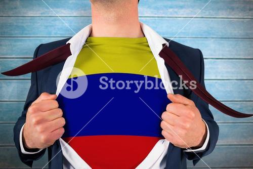 Composite image of businessman opening shirt to reveal colombia flag