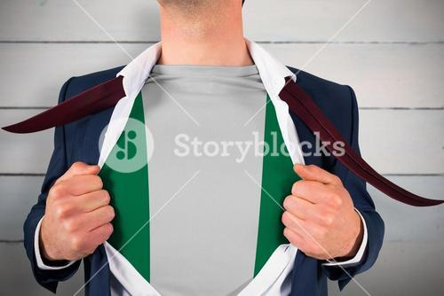 Composite image of businessman opening shirt to reveal nigeria flag
