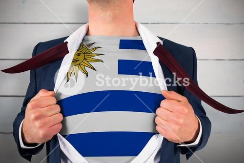 Composite image of businessman opening shirt to reveal uruguay flag