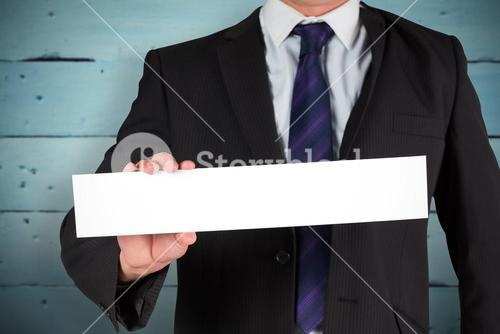 Composite image of businessman showing card