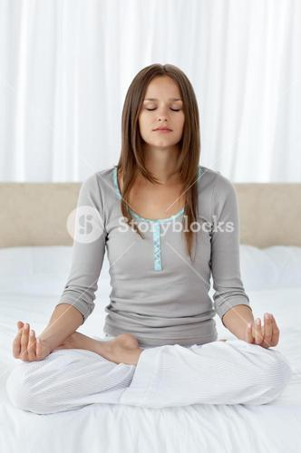 Serene woman doing yoga exercises on the bed