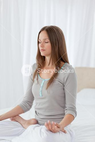 Concentrated woman doing yoga exercises on the bed