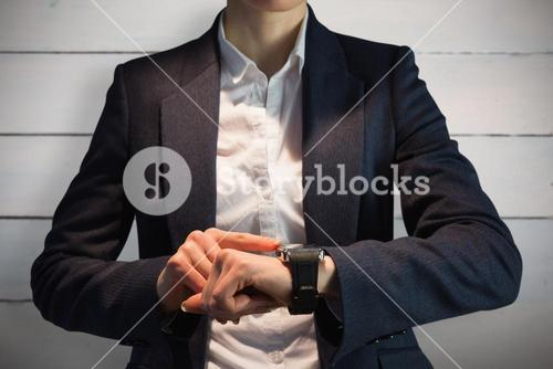 Composite image of businesswoman using watch