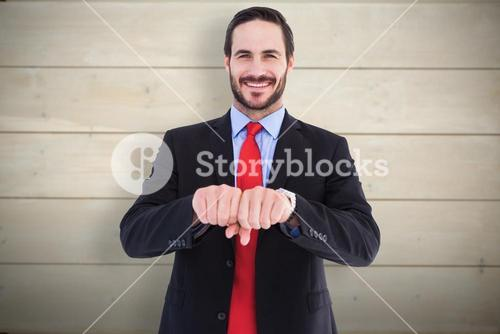 Composite image of smiling businessman with clenched fist in front of him