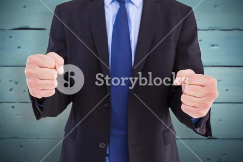 Composite image of businessman with clenched fist in front of him
