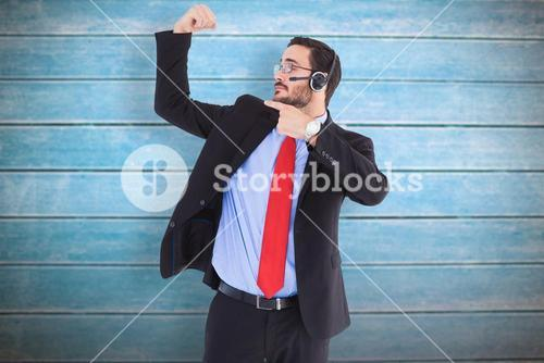 Composite image of smiling man wearing a headset while pointing his bicep