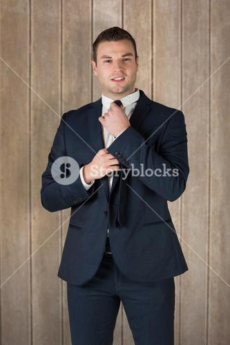 Composite image of businessman tightening his tie