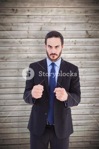 Composite image of angry businessman with closed fists looking at camera