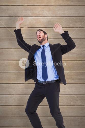 Composite image of shocked businessman standing and pushing up