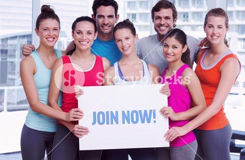 Join now! against fit smiling people holding blank board