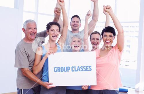 Group classes against portrait of happy fit people holding blank board