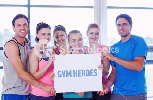 Gym heroes against portrait of a group of fitness class holding blank paper
