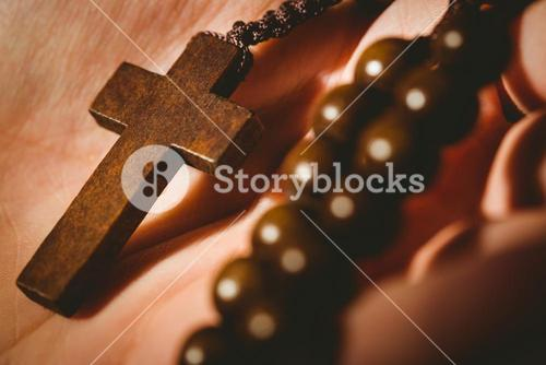 Hand holding wooden rosary beads