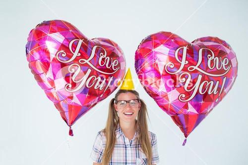 Geeky hipster holding balloons