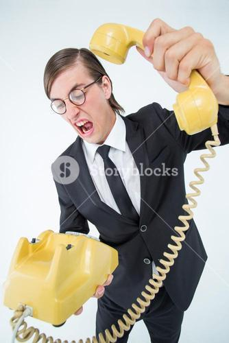 Geeky businessman shouting and hanging up the telephone