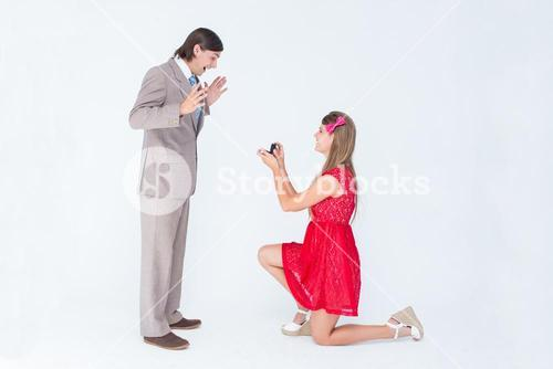 Pretty hipster on bended knee doing a marriage proposal to her boyfriend