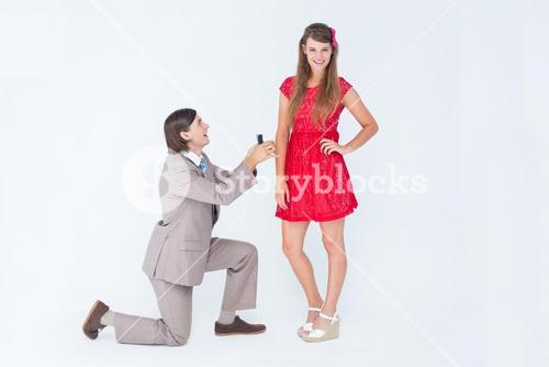 Hipster on bended knee doing a marriage proposal to his girlfriend