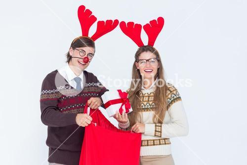Happy geeky hipster couple holding present