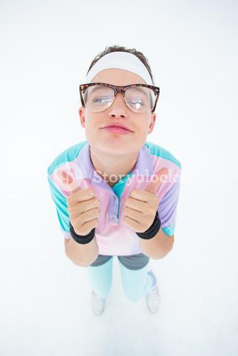 Smiling geeky hipster looking at camera thumbs up