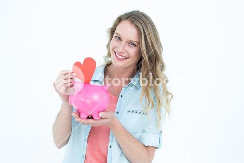 Smiling woman holding piggy bank and red heart