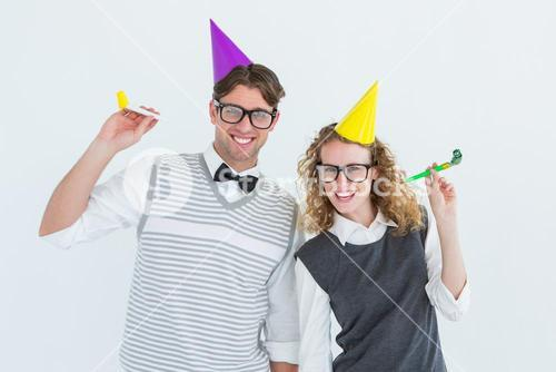 Geeky couple with party hat and party horn
