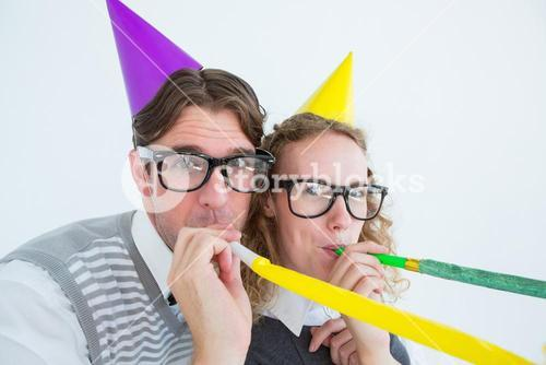 Geeky hipster couple blowing party horn