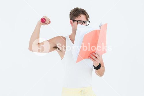 Geeky hipster lifting dumbbells and reading notepad