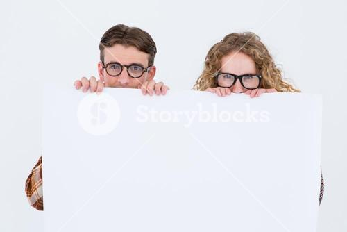 Geeky hipster couple holding poster