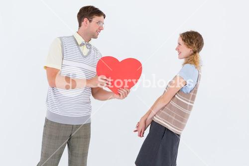 Geeky hipster giving heart card to his girlfriend