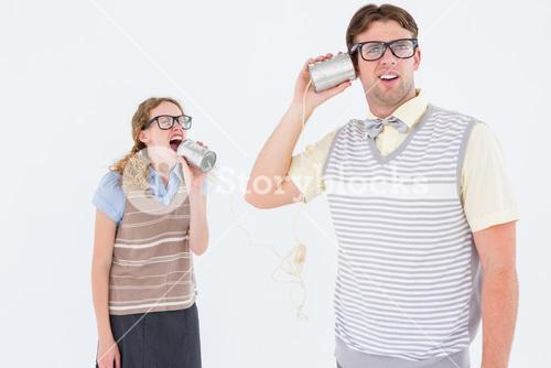Geeky hipster couple speaking with tin can phone