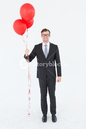 Happy geeky hipster businessman holding balloons