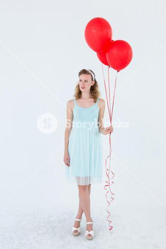 Happy hipster woman holding balloons