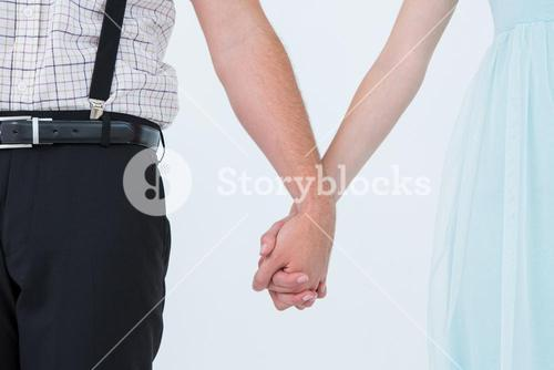 Hipster couple standing hand in hand