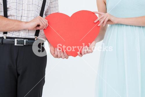 Hipster couple holding heart card