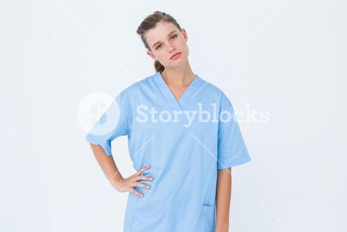 Serious nurse in blue scrubs posing with hand on hip