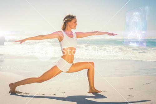 Composite image of gorgeous blonde in warrior pose by the sea