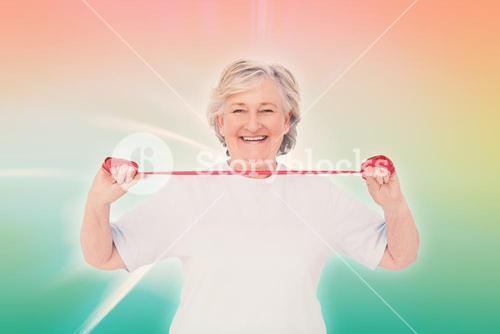 Composite image of senior woman using resistance band