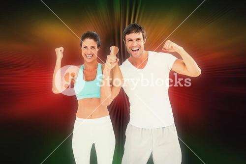 Composite image of cheerful fit couple clenching fists