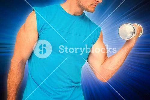 Composite image of close-up mid section of fit man exercising with dumbbell