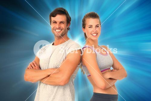 Composite image of portrait of a sporty young couple with arms crossed